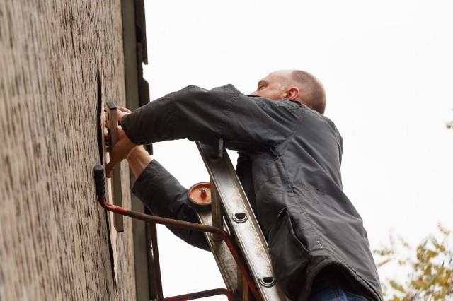 Ruud PE1POA op een ladder met afstandshouder. Ik had een boormal gemaakt van karton, dus eerst moest er afgetekend worden.