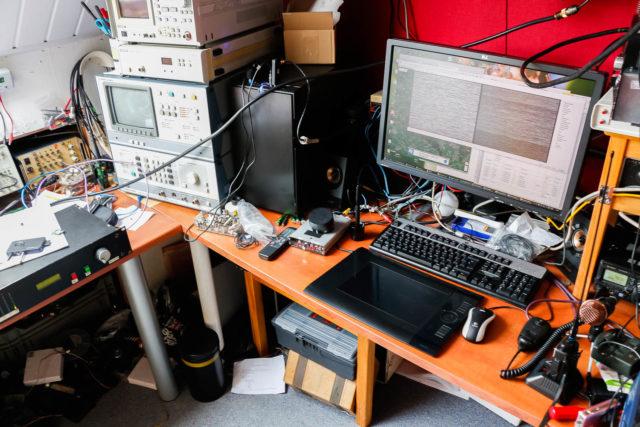 Links de 23cm zender, rechtsboven de 13cm zender en de ontvangers, rechtsonder de set voor phone (2m), in het midden de computer met beeldverwerking en log en links naast het keyboard de sync generator